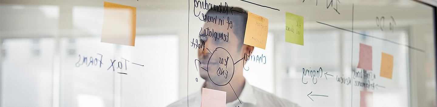 A man reflected in a whiteboard