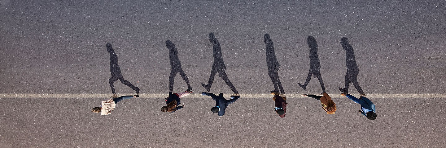 Top down view of people waking in the middle of a street casting shadows
