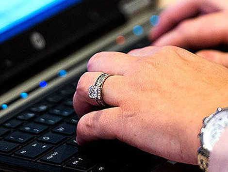 A man's hands wearing a watch and ring typing on a laptop keyboard.
