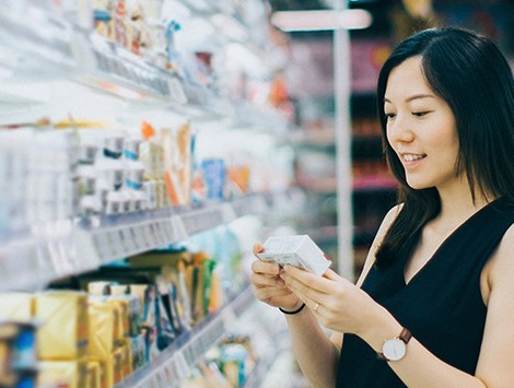 Woman reading nutrition label in supermarket