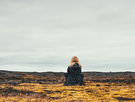Woman sitting near volcanic scenery