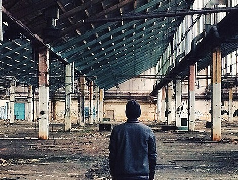 A rear view of a man standing in an abandoned factory