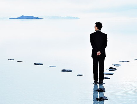 A businessman stands at a fork in the path on a waterway